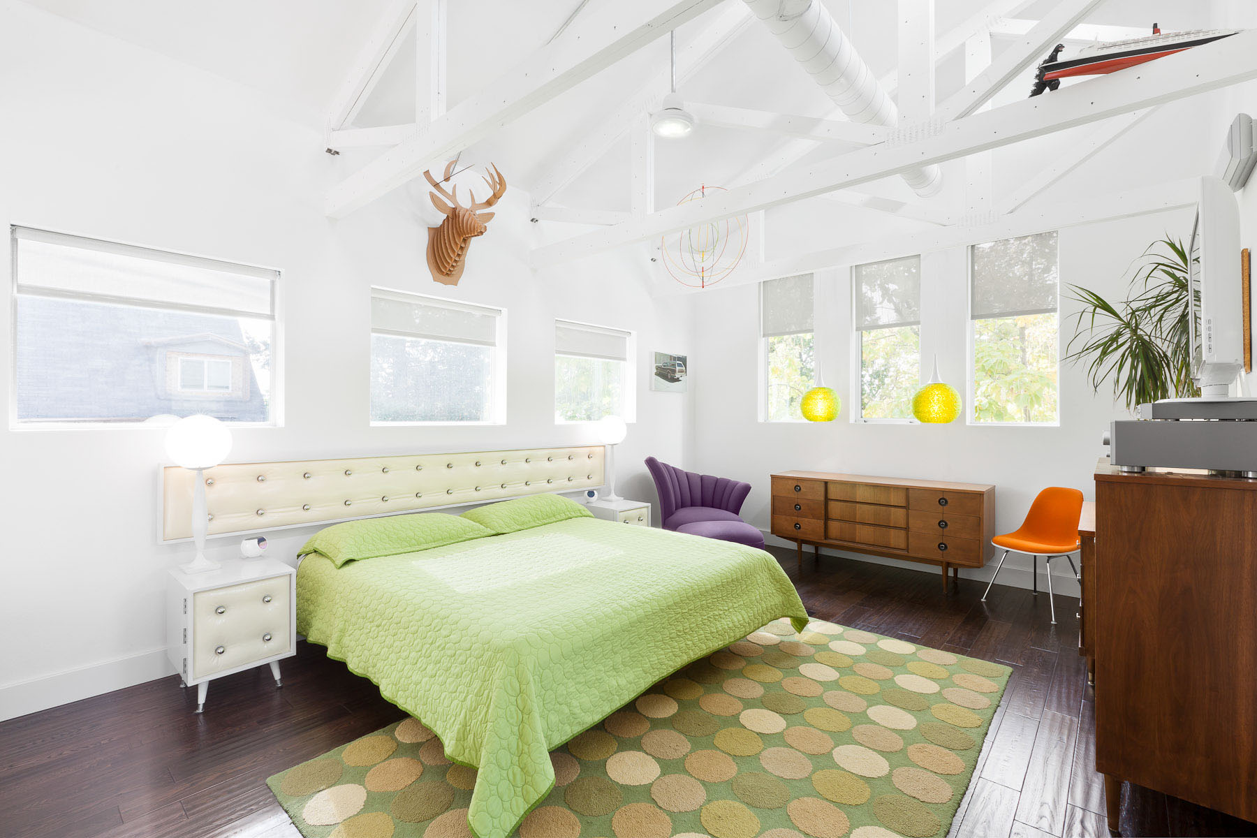 Bright white exposed rafter bedroom designed by Scott Adams Architect with retro style furnishings and appointments in Denver, CO