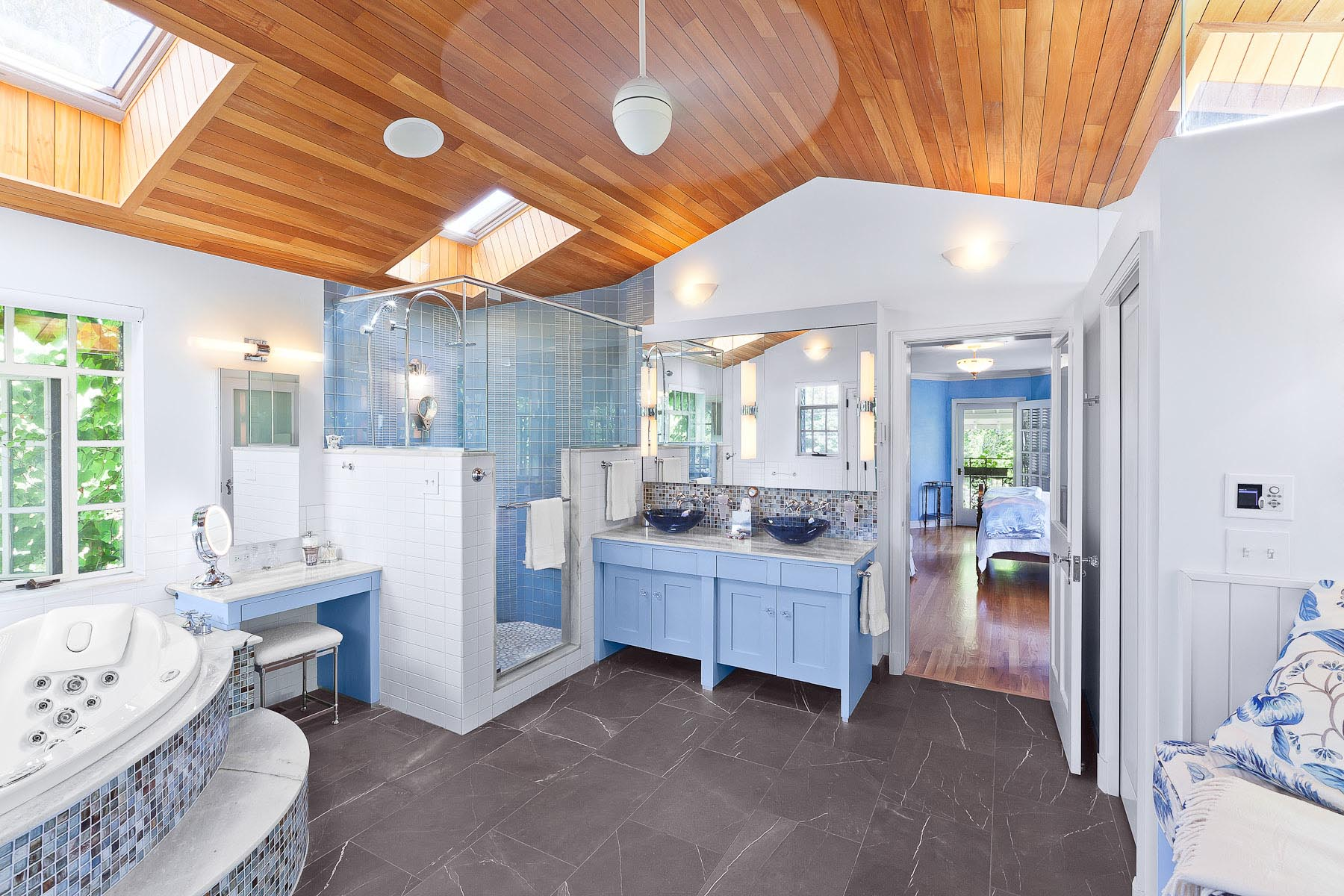 Fresh remodel of a master bathroom in a complete renovation by DAJ Design in Denver, CO featuring blue cabinetry and natural wood ceiling.