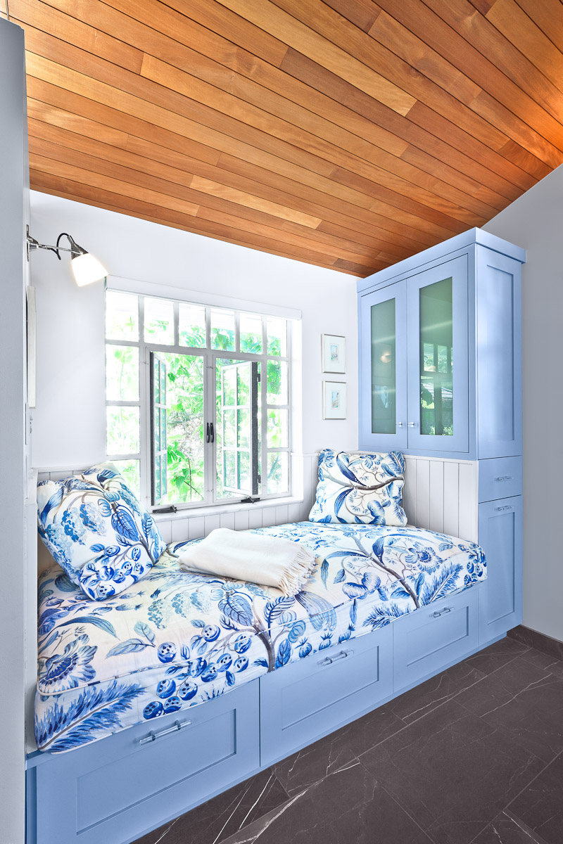 Window reading nook in a master bathroom renovation by DAJ Design featuring blue cabinetry and natural wood ceiling