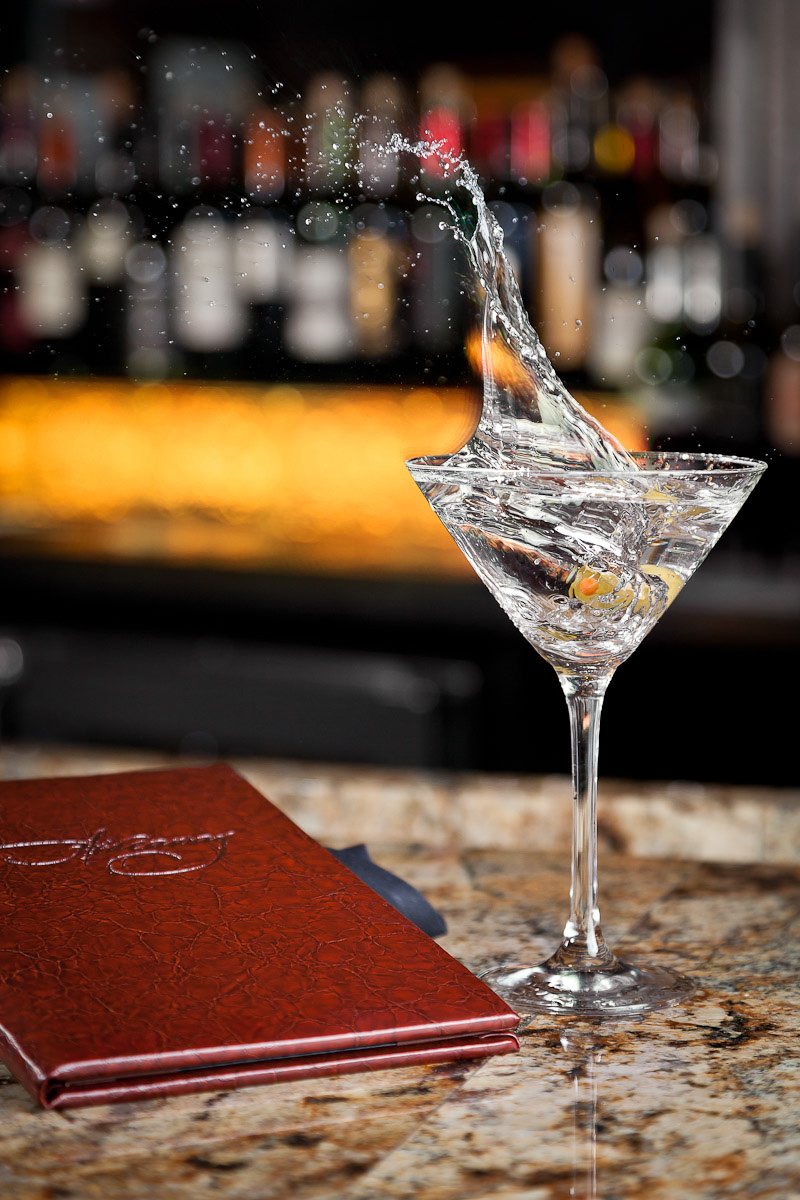 Splash shot of an olive landing in a martini at the bar of Hideaway Steakhouse in Westminster, CO