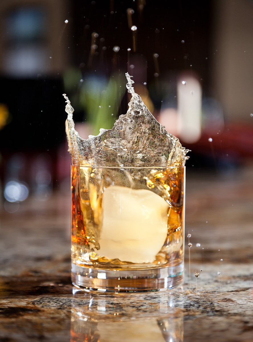 A large ice cube splashing into a glass of scotch on the bar of Hideaway Steakhouse in Westminster, CO