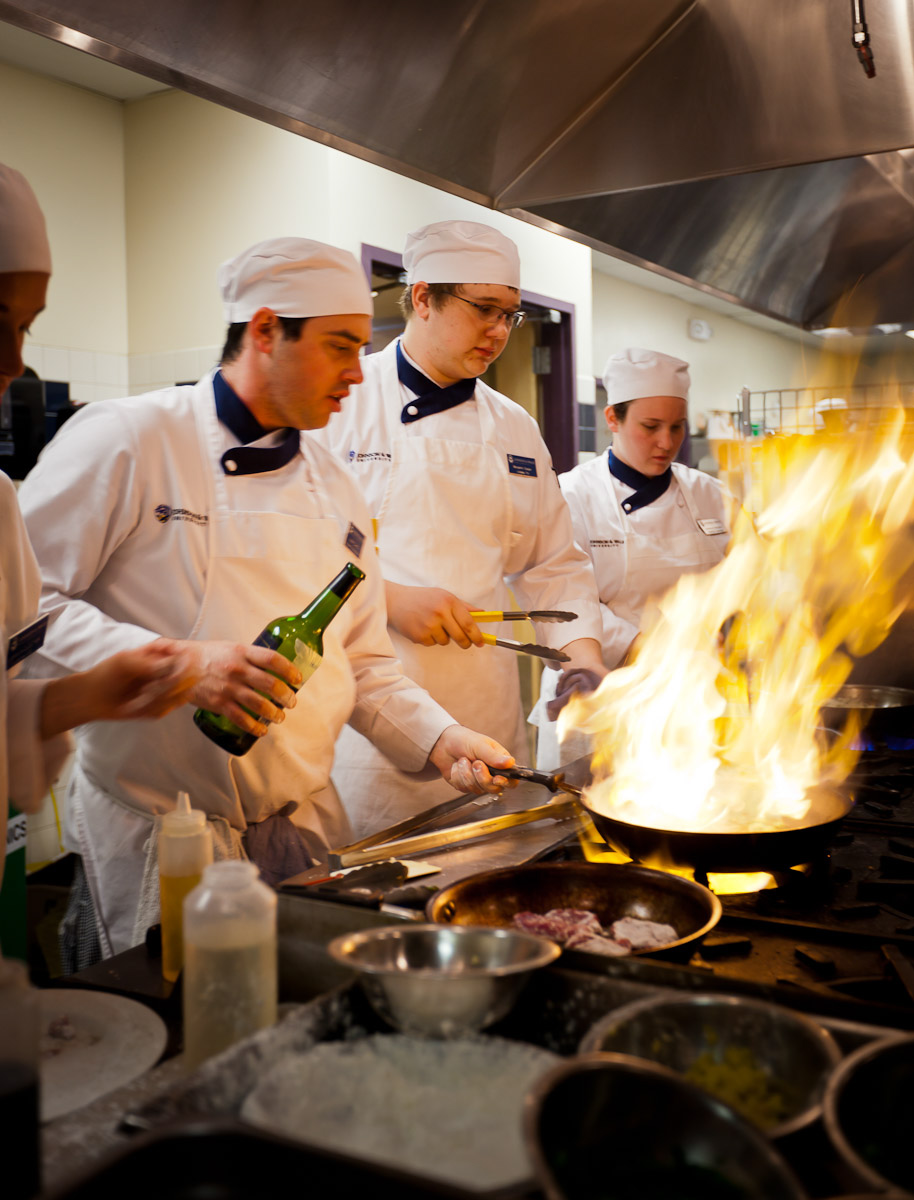 Students at Johnson and Wales University practice flambe techniques in the learning kitchen in Denver, CO