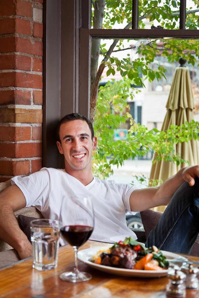 Chef Dakota Soifer poses casually with his lamb shank at Cafe Aion in Boulder, CO