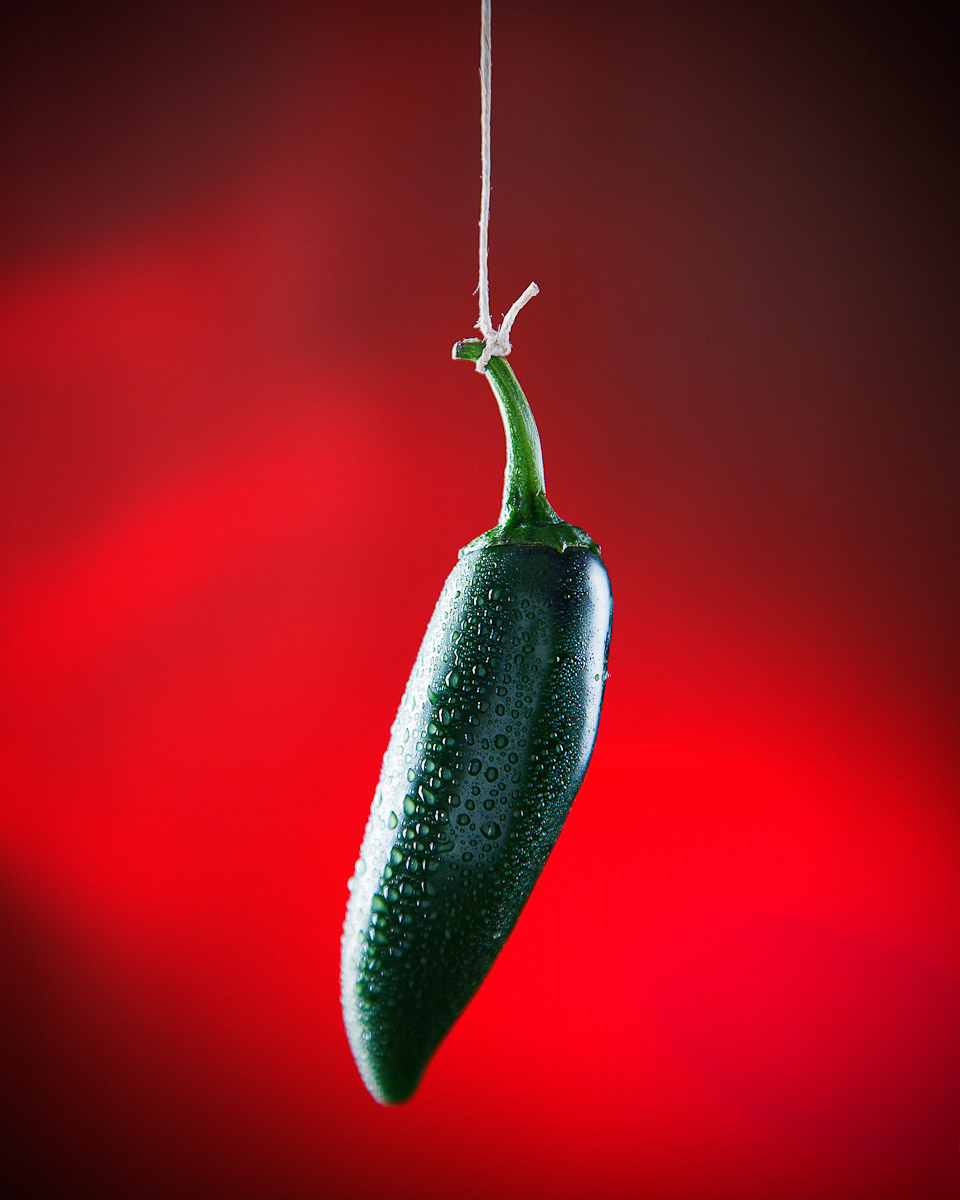 In studio photograph of a fresh jalapeno hanging from a string against a red lit background