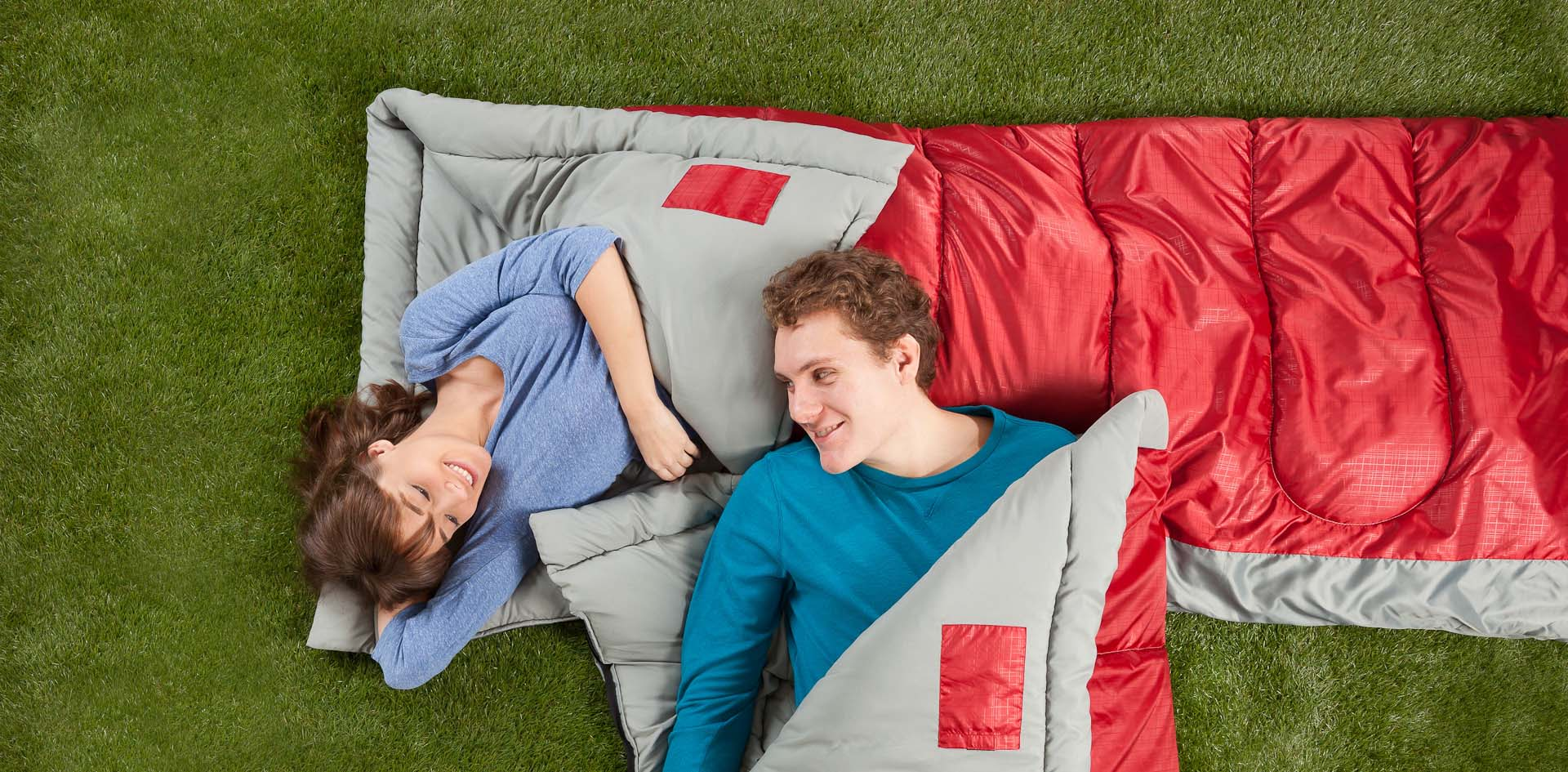 A couple lies in matching Coleman sleeping bags in grass