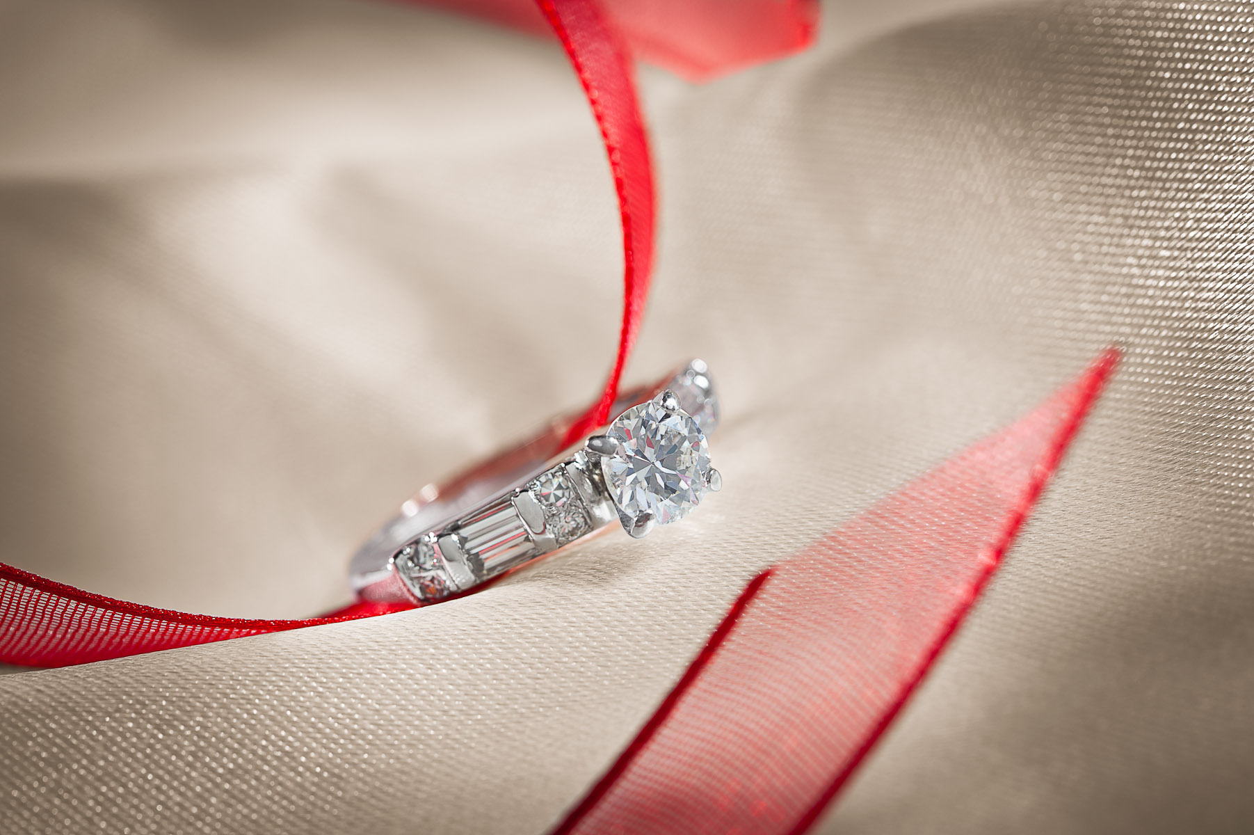 Diamond engagement ring photographed with satin and ribbon