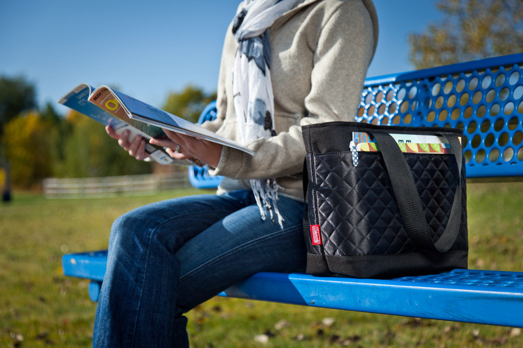 A lifestyle product photo of a Coleman Fashion Tote cooler on a park bench for product packaging, print collateral, and advertising