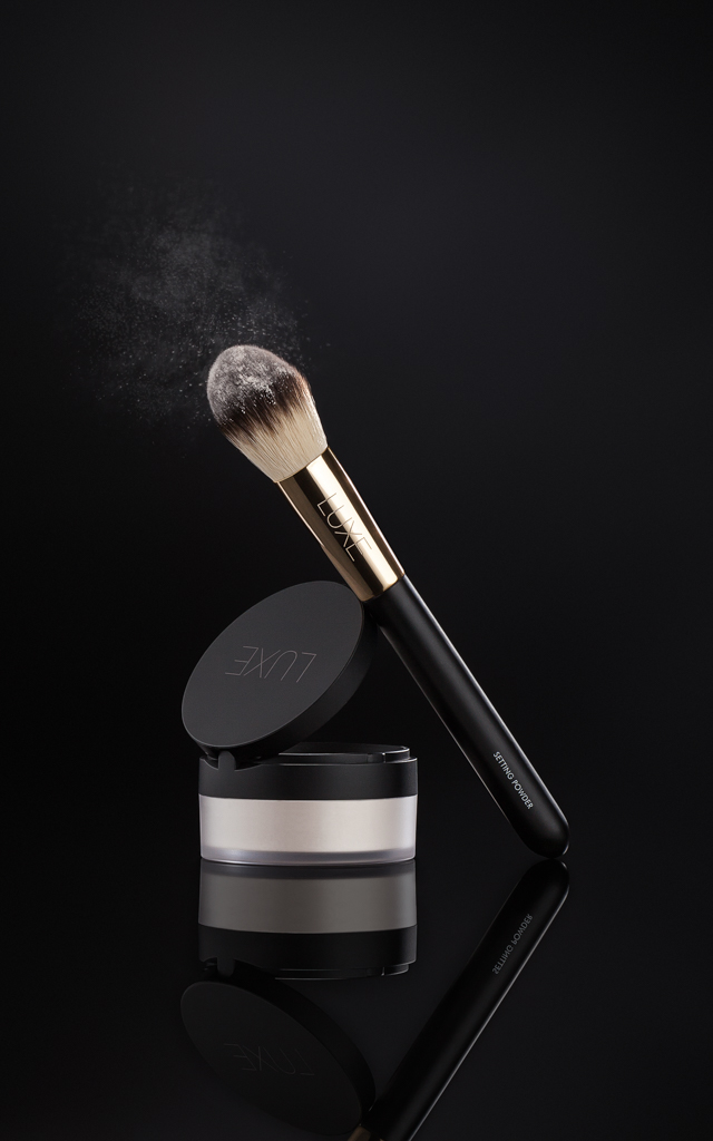 Luxe Setting Powder and brush styled against a black backdrop