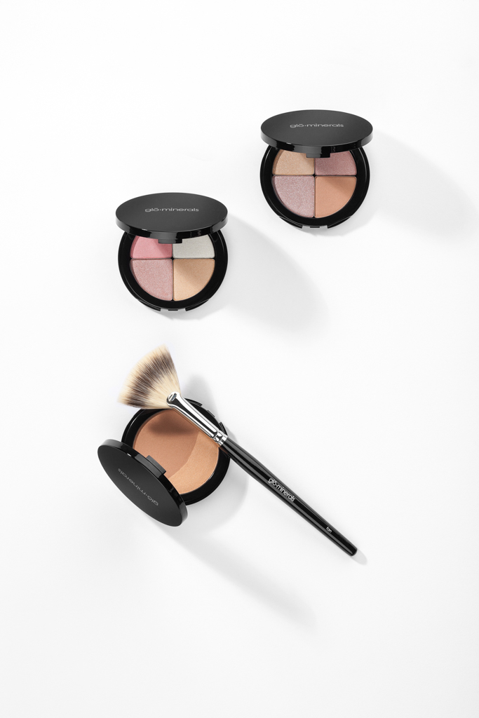 Glo Minerals Cosmetic Compacts with brush on white backdrop
