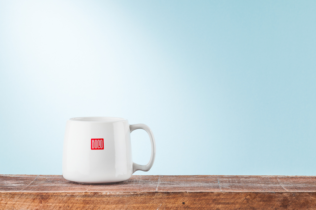 Boco Mug photographed on a wood plank with a light blue background in studio in Littleton, CO for marketing and advertising purposes