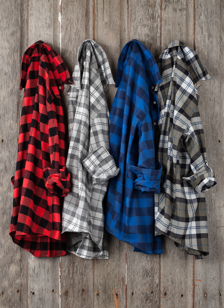 Custom fit flannels on a wood background photographed in studio for marketing purposes.