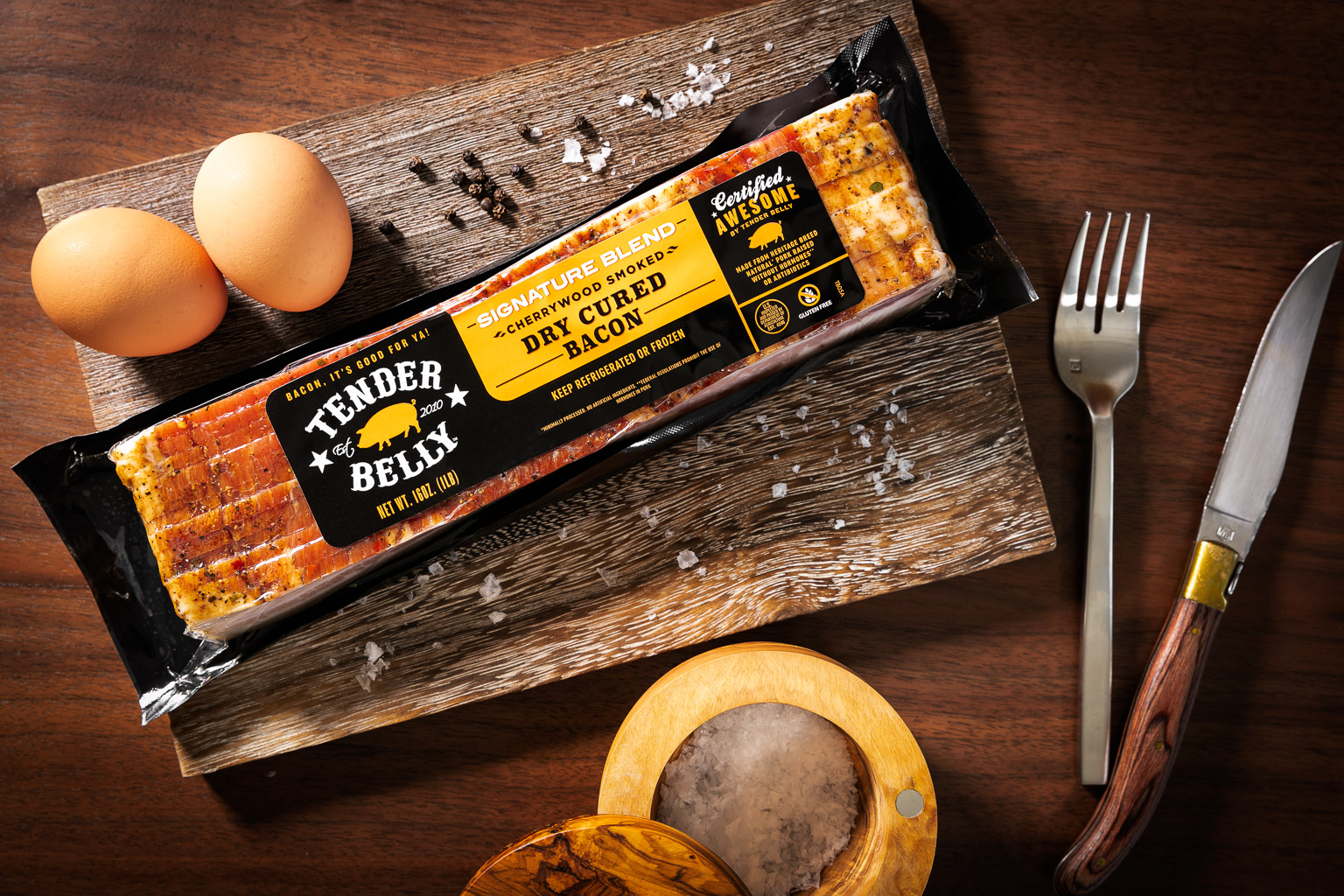 Packaged Tender Belly Cherrywood Smoked Dry Cured Bacon on a wood cutting board with eggs, salt and pepper shot on location in Denver, CO