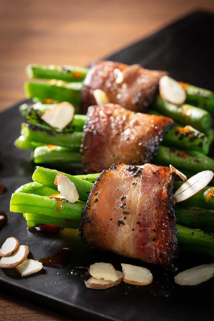 Tender Belly Java Bacon wrapped around fresh green beans prepared by chef Jensen Cummings in Denver, CO